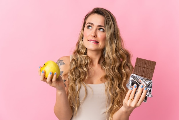 Młoda brazylijka odizolowana na różowo ma wątpliwości, biorąc w jednej ręce czekoladową tabletkę, a drugą jabłko