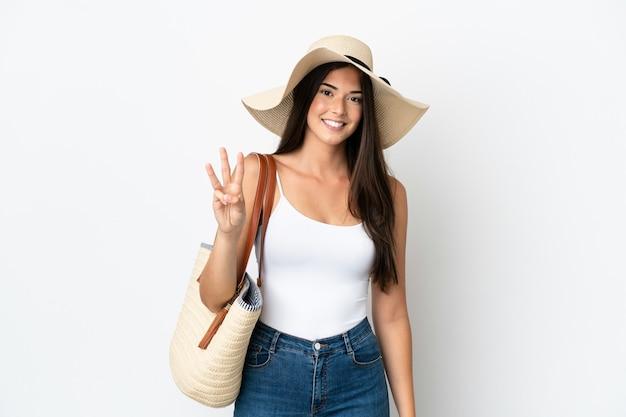 Młoda brazylijka z pamelą trzymająca torbę plażową na białym tle szczęśliwa i licząca trzy palcami