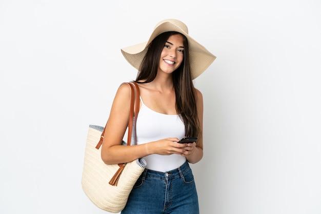 Młoda brazylijka z pamelą trzymająca torbę plażową na białym tle wysyłająca wiadomość za pomocą telefonu komórkowego