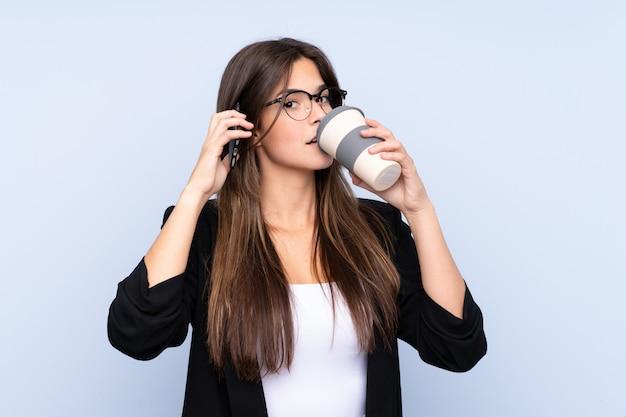 Młoda brazylijska biznesowa kobieta trzyma kawę zabierać i opowiada komórkę