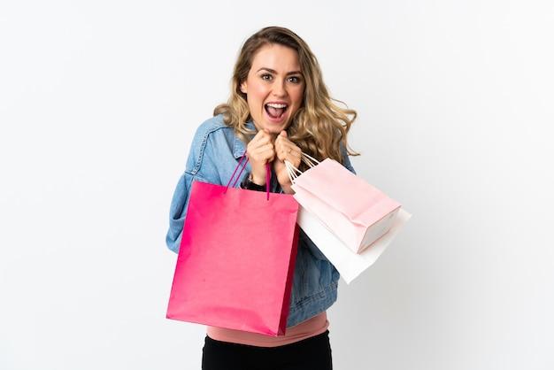Młoda brazylijska kobieta na białym tle gospodarstwa torby na zakupy i zaskoczony