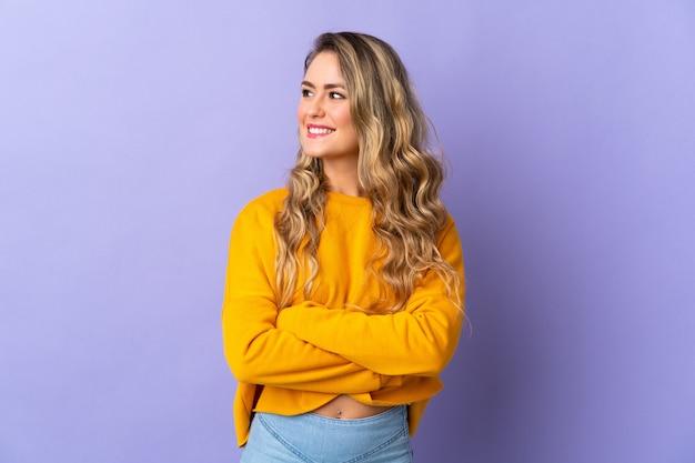 Młoda brazylijska kobieta na białym tle na fioletowej ścianie, patrząc z boku i uśmiechnięta