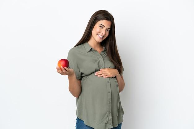 Młoda brazylijska kobieta na białym tle w ciąży i trzymająca jabłko