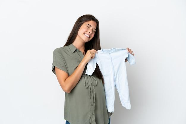 Młoda brazylijska kobieta na białym tle w ciąży i trzymająca ubrania dla dzieci