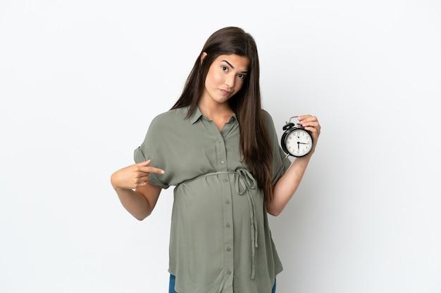 Młoda brazylijska kobieta na białym tle w ciąży i trzymająca zegar z zestresowanym wyrazem twarzy