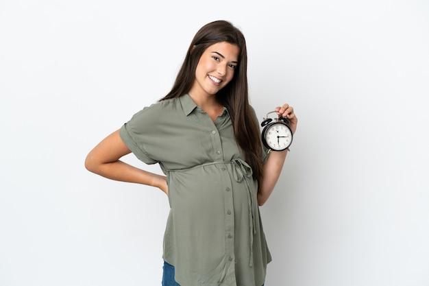Młoda brazylijska kobieta na białym tle w ciąży i trzymająca zegar