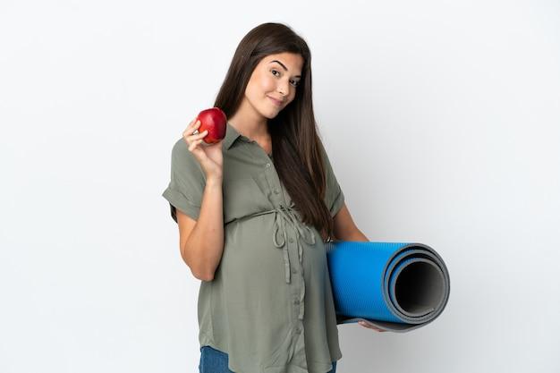 Młoda brazylijska kobieta na białym tle w ciąży trzyma jabłko i idzie na zajęcia jogi