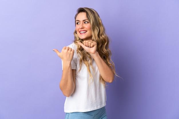 Młoda brazylijska kobieta na fioletowym tle, wskazując na bok, aby przedstawić produkt