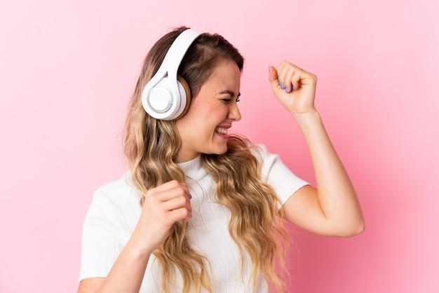 Młoda brazylijska kobieta na różowym tle słuchania muzyki i tańca