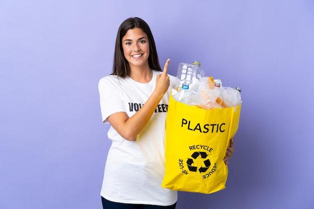 Młoda brazylijska kobieta trzyma torbę pełną plastikowych butelek do recyklingu na białym tle na fioletowej ścianie, wskazując na bok, aby przedstawić produkt