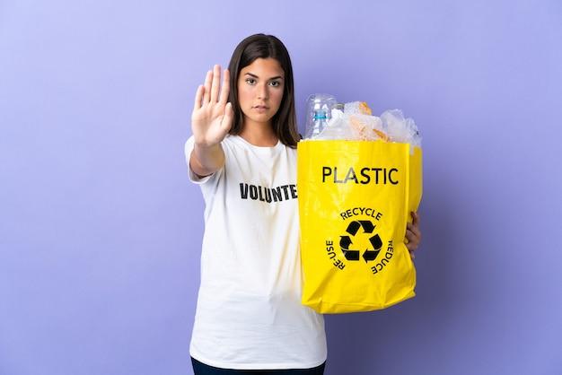 Młoda brazylijska kobieta trzyma torbę pełną plastikowych butelek do recyklingu na białym tle na fioletowej ścianie, wykonując gest stopu