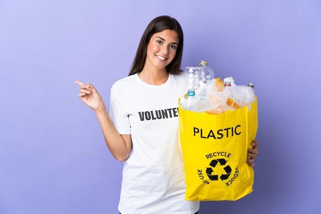 Młoda brazylijska kobieta trzyma torbę pełną plastikowych butelek do recyklingu na białym tle na fioletowy palec wskazujący na bok