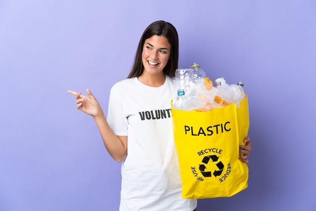 Młoda brazylijska kobieta trzyma torbę pełną plastikowych butelek do recyklingu na białym tle
