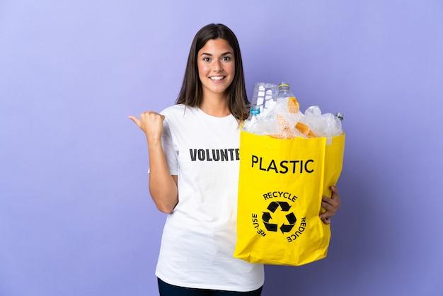 Młoda brazylijska kobieta trzyma torbę pełną plastikowych butelek do recyklingu odizolowane na fioletowo, wskazując na bok, aby przedstawić produkt