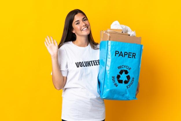 Młoda brazylijska kobieta trzyma worek recyklingu pełnego papieru do recyklingu na białym tle