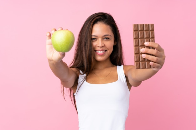 Młoda brazylijska kobieta z jabłkiem i czekoladą nad różową ścianą