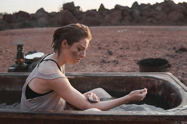 Młoda brudna kobieta siedzi w wannie i myje swoje ciało na zewnątrz na pustyni