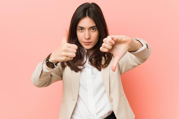 Młoda brunetka biznesowa kobieta na różowym tle pokazuje kciuki w górę i w dół, trudno wybrać koncepcję