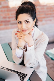 Młoda brunetka bizneswoman o uroczych oczach, delikatne dłonie z czerwonym manicure sobie