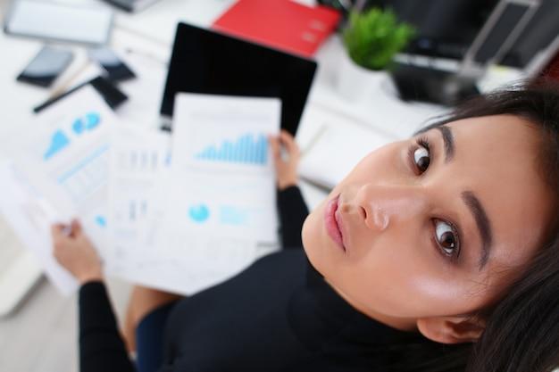 Młoda brunetka bizneswoman studiuje dokumenty w biurze