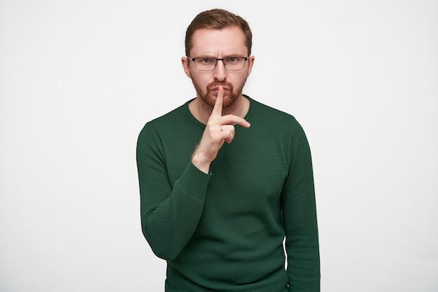 Młoda brunetka brodaty facet w okularach, podnosząc rękę z gestem ciszy podczas pozowania, marszcząc brwi i patrząc poważnie