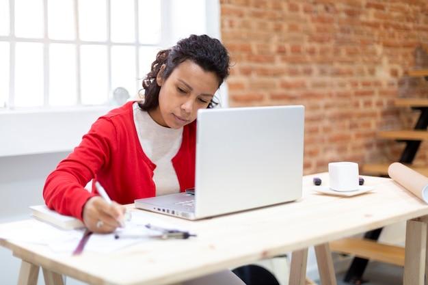 Młoda brunetka ciężko pracuje w swoim domowym biurze. miejsce na tekst. koncepcja planów i nowych projektów.