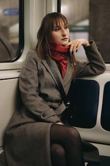Młoda brunetka dama w płaszczu w samochodzie metra wygląda przez okno