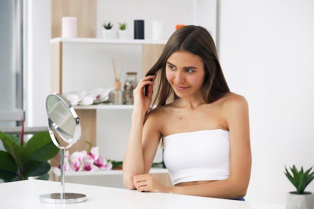 Młoda brunetka dba o swoją skórę, stojąc przed lustrem, ciesząc się zabiegami kosmetycznymi dla siebie, czule się uśmiechając