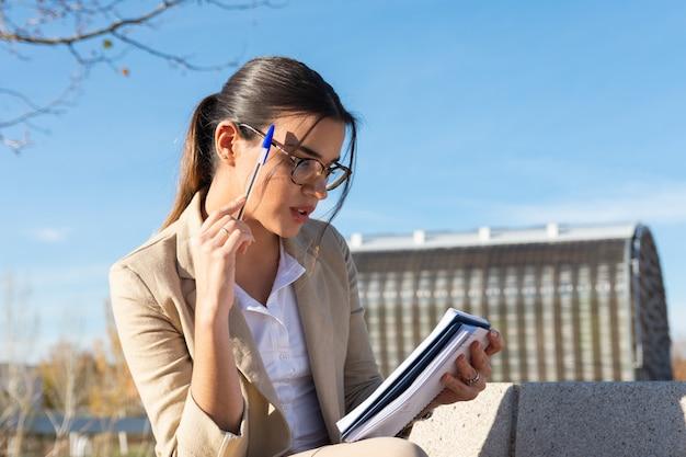Młoda brunetka dziewczyna pracuje na ławce w parku poza jej biurem. pisanie w jej programie. koncepcja biznesowa, technologia i telepraca.
