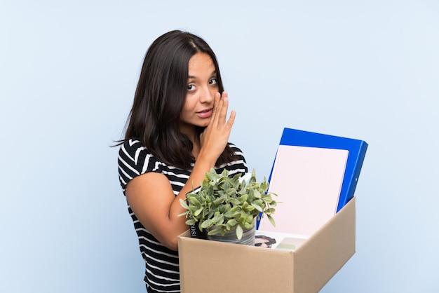 Młoda brunetka dziewczyna robi ruch, podnosząc pudełko pełne rzeczy szepcząc coś
