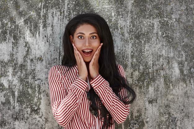 Młoda brunetka dziewczyna stojąca na szarej ścianie, patrząc na usta kamery, otworzyła zaskoczony zbliżenie