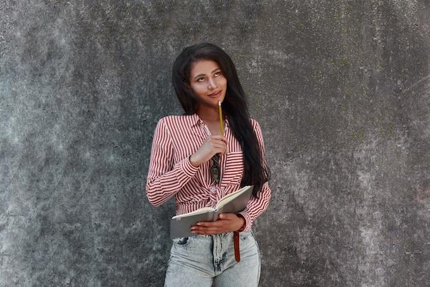 Młoda brunetka dziewczyna stojąca na szarej ścianie trzyma notatnik patrząc w górę planując dzień uśmiechając się szczęśliwa