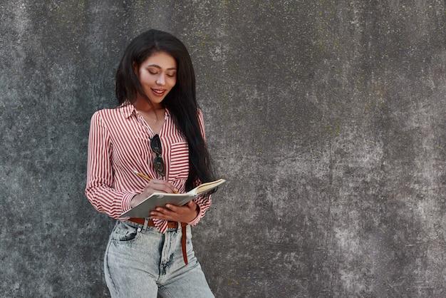 Młoda brunetka dziewczyna stojąca na szarej ścianie trzymająca notatnik robiąca notatki uśmiechnięta szczęśliwa