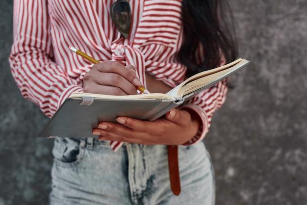 Młoda brunetka dziewczyna stojąca na szarej ścianie trzymająca notatnik robiąca notatki zbliżenie notes