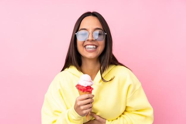Młoda brunetka dziewczyna trzyma lody cornet na pojedyncze różowe, dużo uśmiecha się