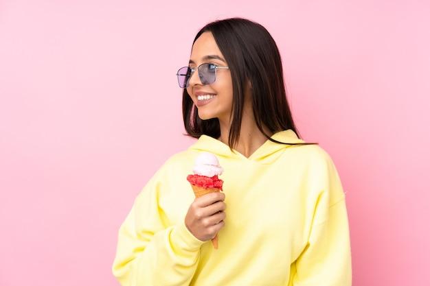 Młoda brunetka dziewczyna trzyma lody cornet na pojedyncze różowe ściany patrząc z boku