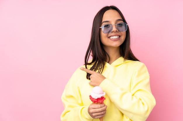 Młoda brunetka dziewczyna trzyma lody cornet na pojedyncze różowe, wskazując na bok, aby przedstawić produkt