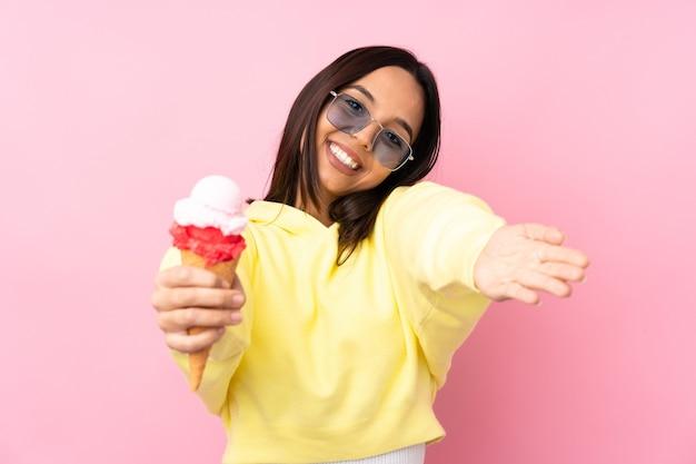 Młoda brunetka dziewczyna trzyma lody kornetkowe na odosobnionej różowej ścianie prezentując i zapraszając do przyjścia z ręką