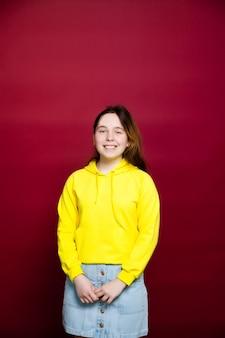 Młoda brunetka dziewczyna ubrana stylowa żółta bluza z kapturem stojący na białym tle nad czerwoną ścianą