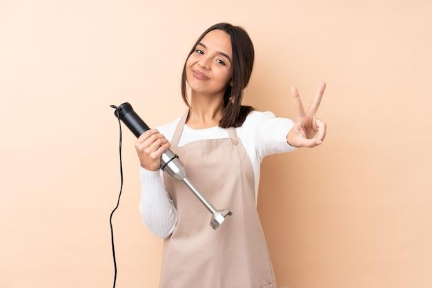 Młoda brunetka dziewczyna używa blendera ręcznego na białym tle, uśmiechając się i pokazując znak zwycięstwa