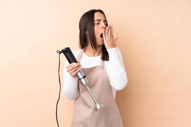 Młoda brunetka dziewczyna używa blendera ręcznego na białym tle, ziewa i zakrywa ręką szeroko otwarte usta mouth