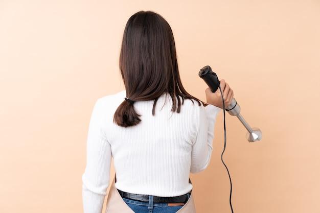 Młoda brunetka dziewczyna używa blendera ręcznego na na białym tle w pozycji tylnej