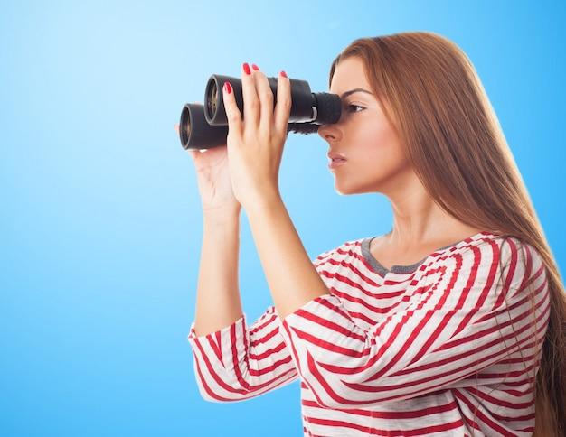 Młoda brunetka dziewczyna w koszuli w paski szpiegostwo przez lornetkę