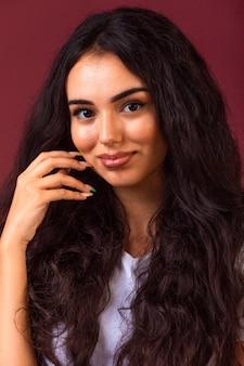 Młoda brunetka dziewczyna z długimi i kręconymi włosami promująca jesienny styl makijażu.