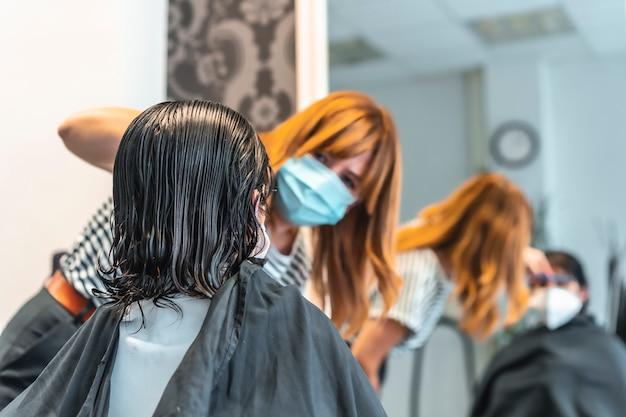 Młoda brunetka dziewczyna z maską w fryzjera cięcie włosy odbicie w lustrze. środki bezpieczeństwa dla fryzjerów podczas pandemii covid-19. nowy normalny, koronawirus, dystans społeczny