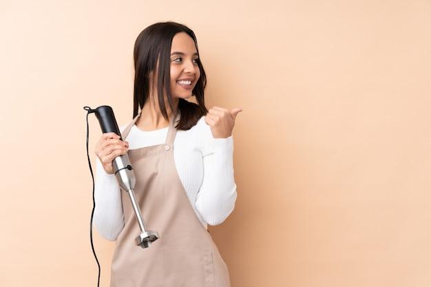Młoda brunetka dziewczyna za pomocą ręcznego blendera na pojedyncze ściany, wskazując w bok, aby przedstawić produkt