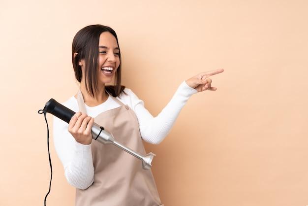 Młoda brunetka dziewczyna za pomocą ręcznego miksera na izolowanej ścianie wskazując palcem na bok i prezentuje produkt