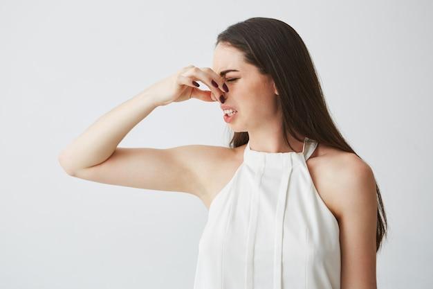 Młoda brunetka dziewczyna zamknięcia obejmujące nos. nieprzyjemny zapach.