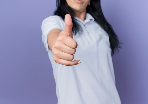 Młoda brunetka dziewczynka kaukaski kciuki do góry na białym tle na fioletowej ścianie