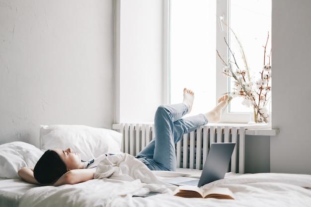 Młoda Brunetka Kaukaski Kobieta Leżąc Na łóżku, Relaksując Się Rano W Domu I Wyglądać Przez Okno. Premium Zdjęcia